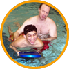 image of special recreation professional swimming with disabled teen